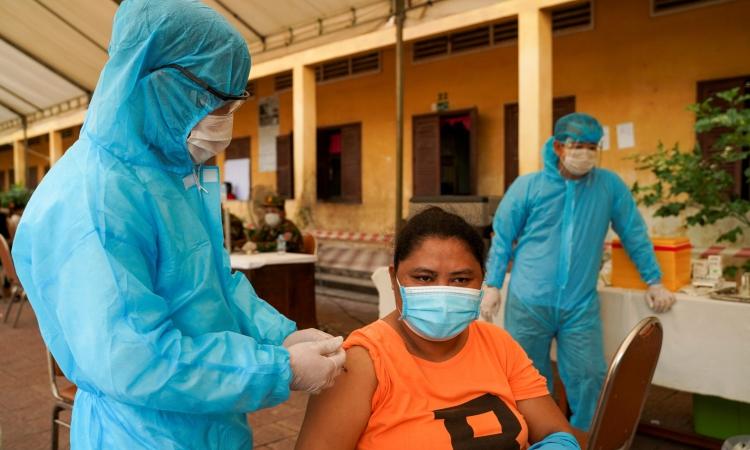 Binh sĩ Campuchia tiêm vaccine Covid-19 cho một người ở Phnom Penh, Campuchia hồi tháng 5. Ảnh: Reuters.