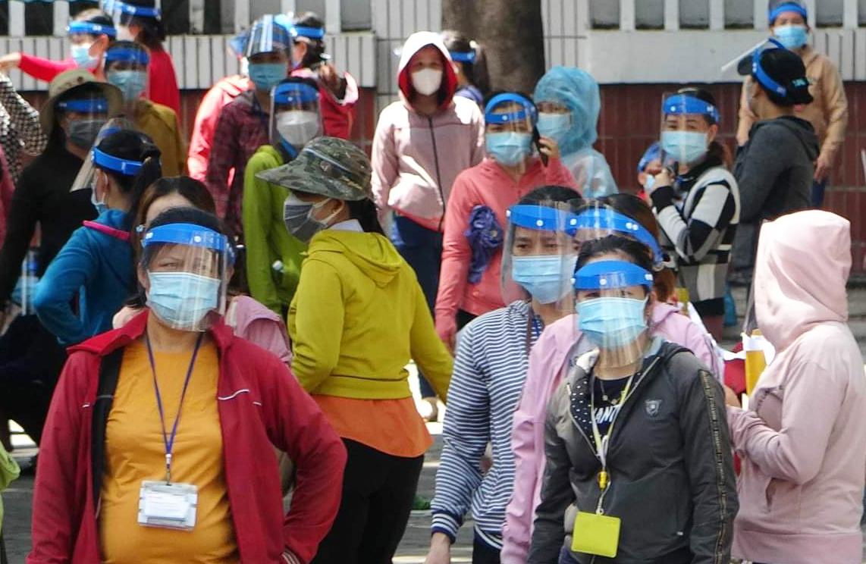 Công nhân Pouchen Việt Nam ra về sau khi công ty đóng cửa để phòng dịch trong 14 ngày. Ảnh: Thái Hà
