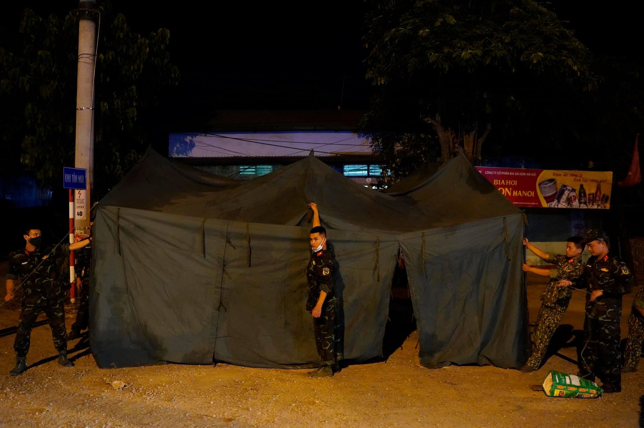 Tại chốt 13, chốt kiểm dịch huyện Chương Mỹ trên quốc lộ 6, Đội CSGT số 12 phối hợp với 10 chiến sĩ Lữ đoàn 201 dựng lều bạt dã chiến bên vệ đường. Ảnh: Gia Chính