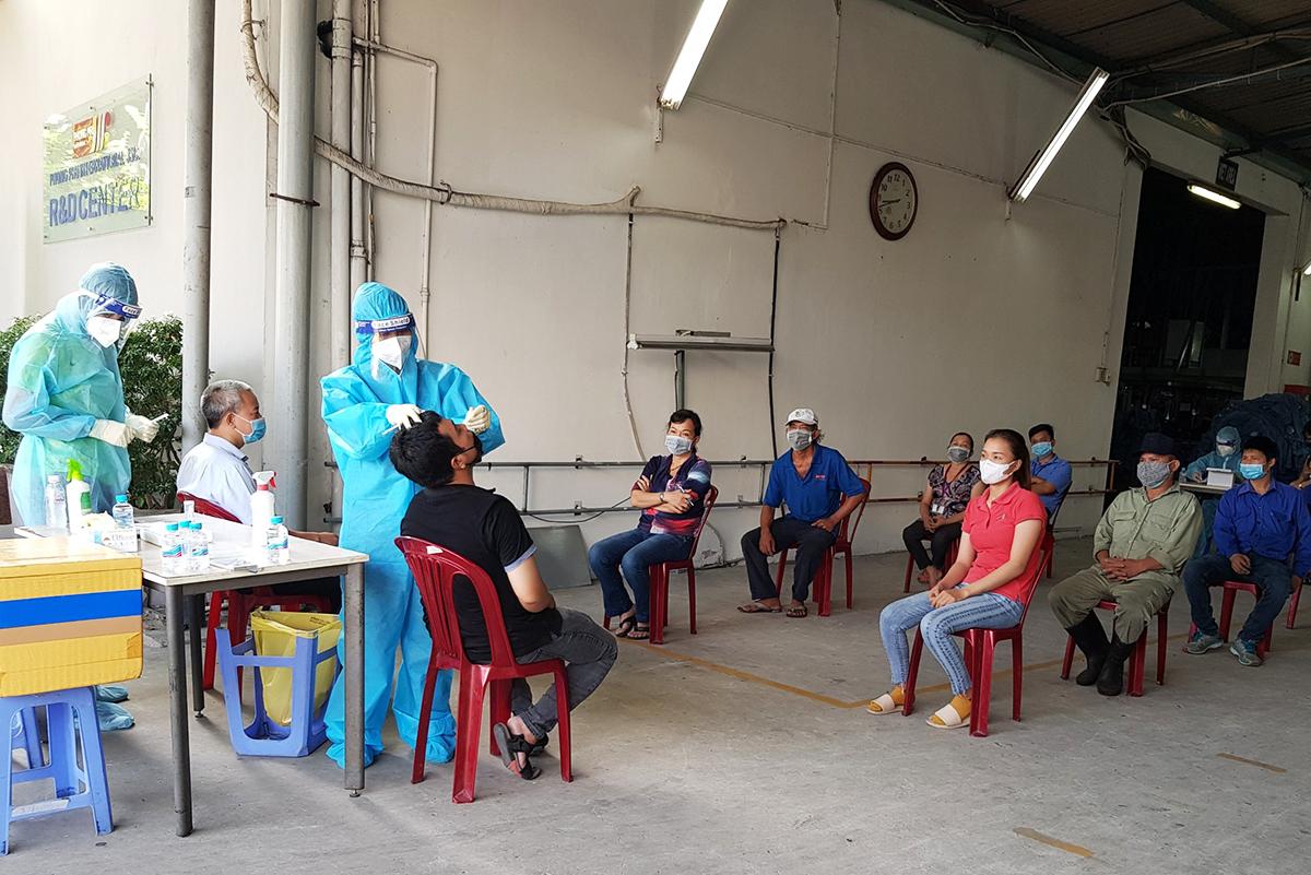 Công nhân Công ty quốc tế Phong Phú xét nghiệm trước khi vào ăn ở tại nhà máy, sáng 13/7. Ảnh: An Phương.