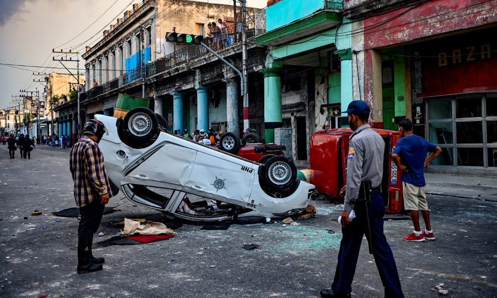 Ô tô bị lật úp trên đường phố Havana, Cuba, hôm 11/7. Ảnh: AFP.