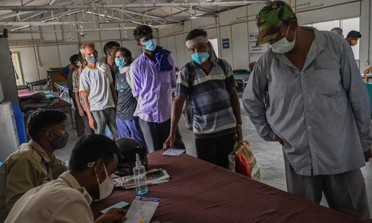 Người vô gia cư xếp hàng chờ được hỗ trợ đăng ký tiêm chủng trực tuyến tại một trại tạm trú ở thủ đô New Delhi, Ấn Độ. Ảnh: AFP.