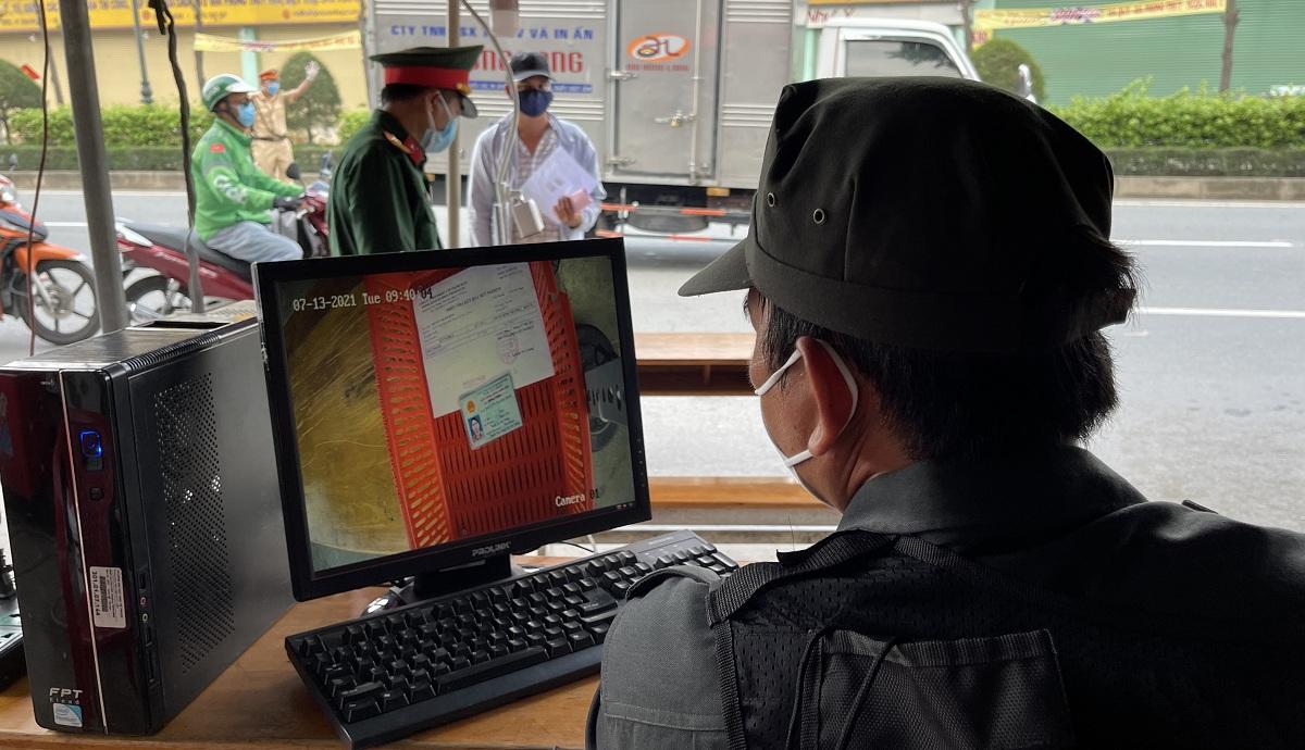 Lực lượng chức năng kiểm tra giấy tờ người qua chốt bằng camera soi chiếu. Ảnh: Hà An.