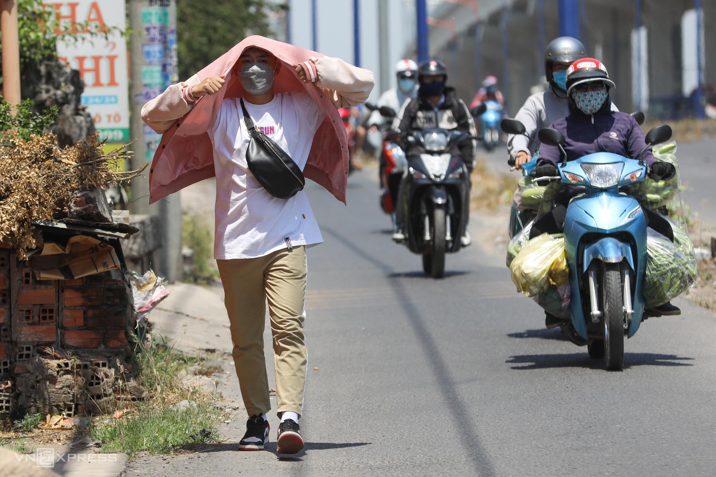 Một sinh viên đi bộ ra trạm xe buýt trong nắng nóng 38 độ C ở TP HCM hồi tháng ba. Ảnh: Quỳnh Trần.