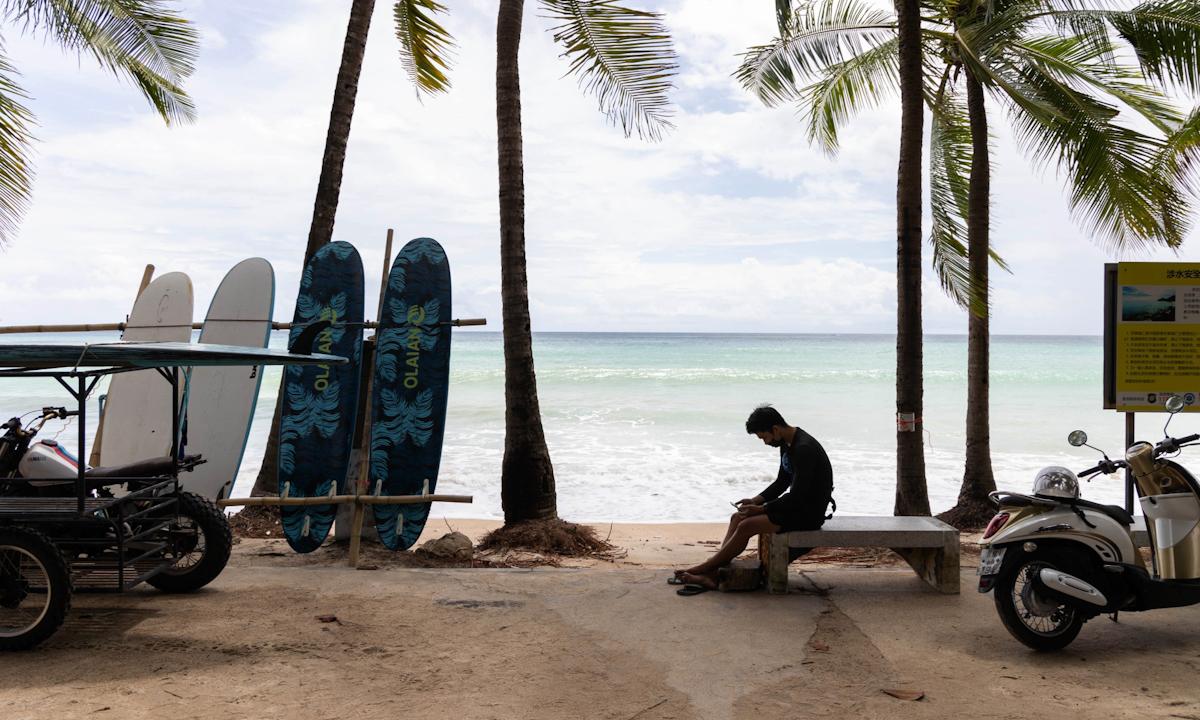 Một người cho thuê đồ lướt sóng tại bãi biển Kamala ở Phuket hôm 26/6. Ảnh: Bloomberg.