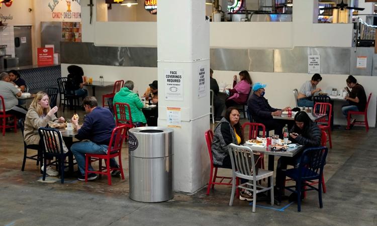 Người dân tập trung trong một nhà hàng ở Grand Central Market, Los Angeles, Mỹ, hôm 17/3. Ảnh: AP.