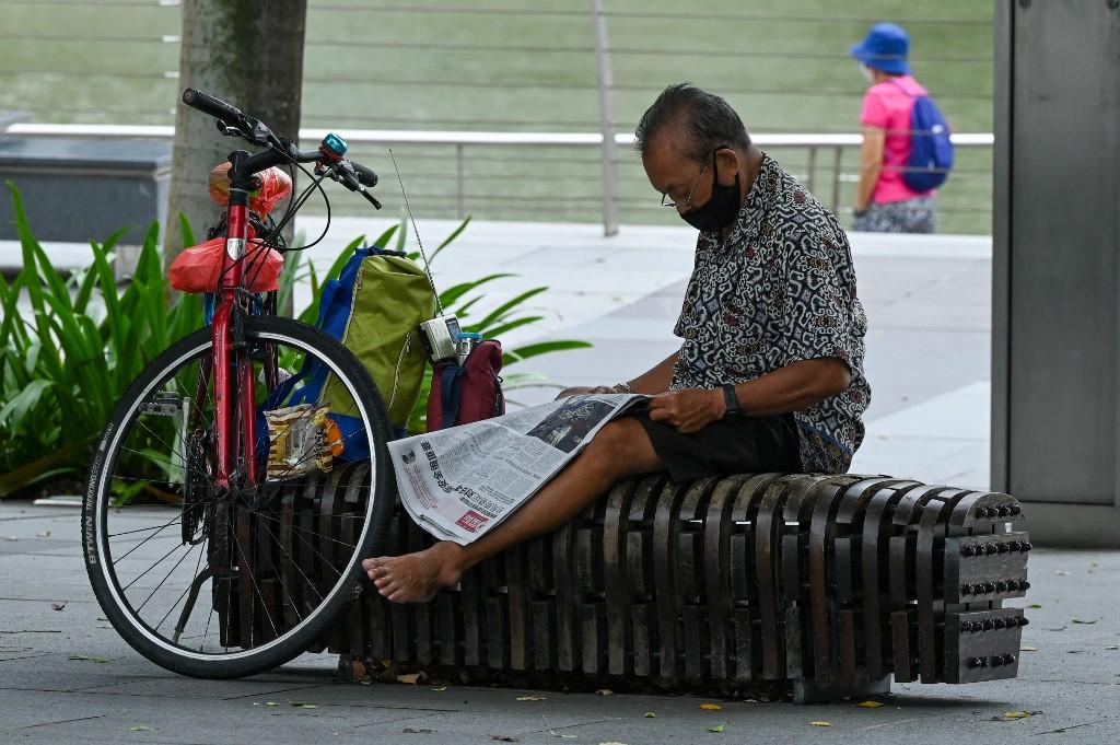 Một người ngồi đọc báo ở Singapore ngày 14/7. Ảnh: AFP.