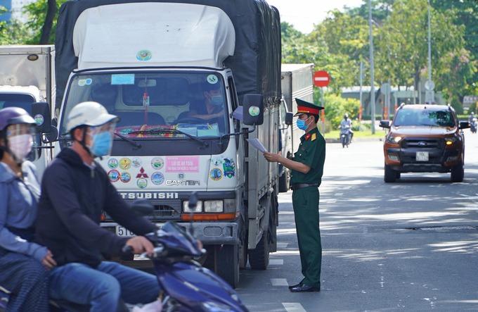 Lực lượng chức năng kiểm tra giấy tờ tài xế tại chốt kiểm soát trước Bến xe Miền Đông trên đường Đinh Bộ Lĩnh, quận Bình Thạnh, sáng 10/7. Ảnh:Gia Minh.