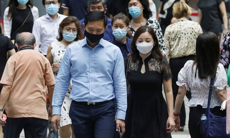 Người dân đeo khẩu trang trên một con phố ở trung tâm Singapore vào giờ nghỉ trưa ngày 12/5. Ảnh: Reuters.
