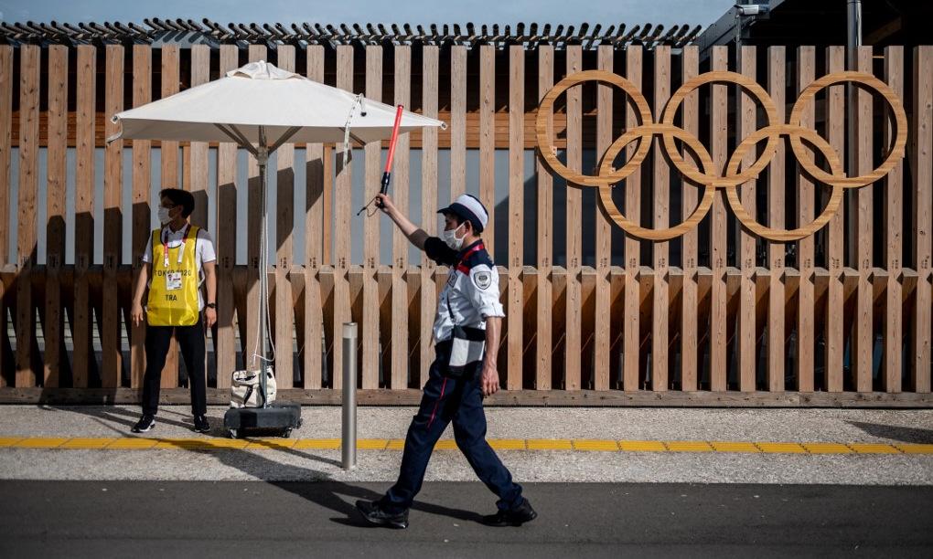 Nhân viên ban tổ chức bên ngoài làng Olympic ở Tokyo hôm 15/7. Ảnh: AFP.