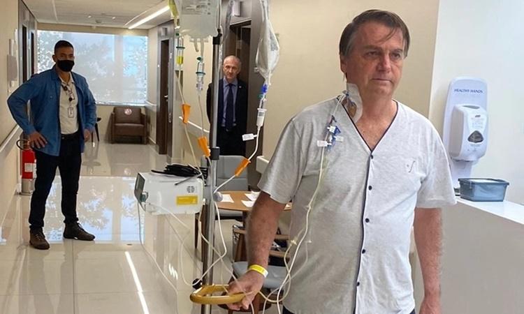 Tổng thống Jair Bolsonaro đi bộ trong hành lang bệnh viện Vila Nova Star ở Sao Paulo ngày 16/7. Ảnh: Twitter/@jairbolsonaro.