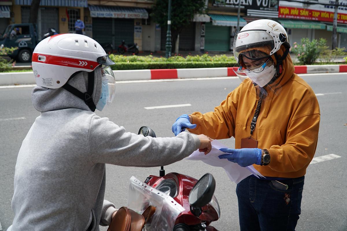 Tổ tuần tra thực hiện Chỉ thị 16 của UBND phường 8, TP Vũng Tàu kiểm tra một phụ nữ chạy xe máy từ chỗ làm về nhà, trưa 16/7. Ảnh: Trường Hà.