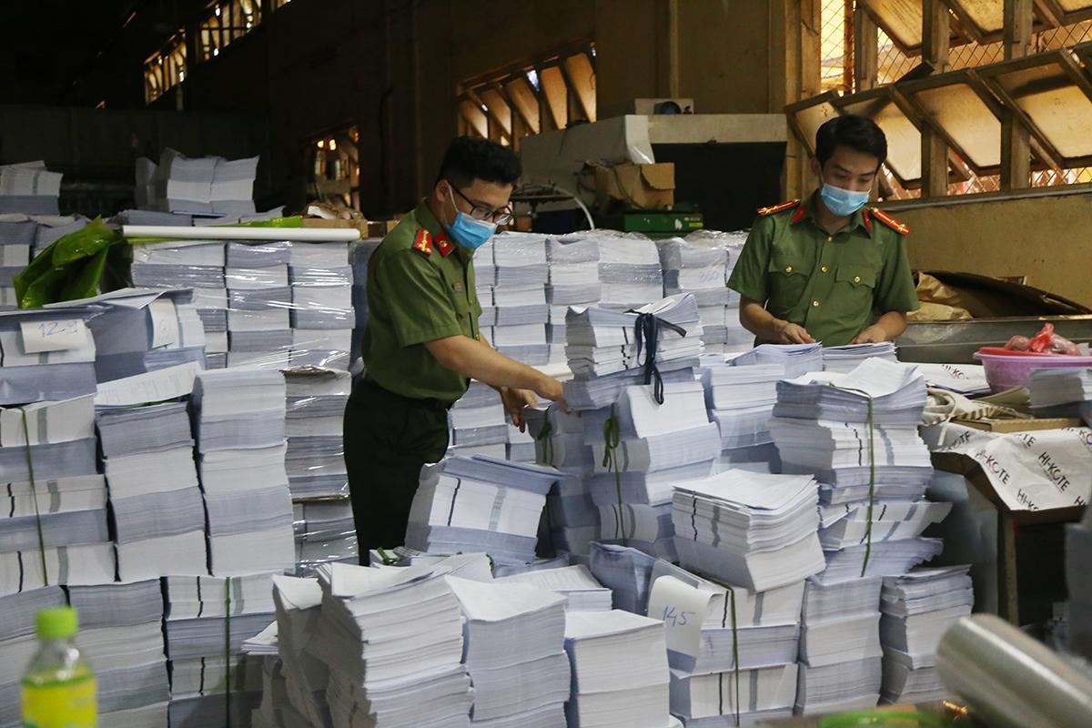 Nhà chức trách khám xét cơ sở sản xuất sách lậu. Ảnh: Phạm Dự.