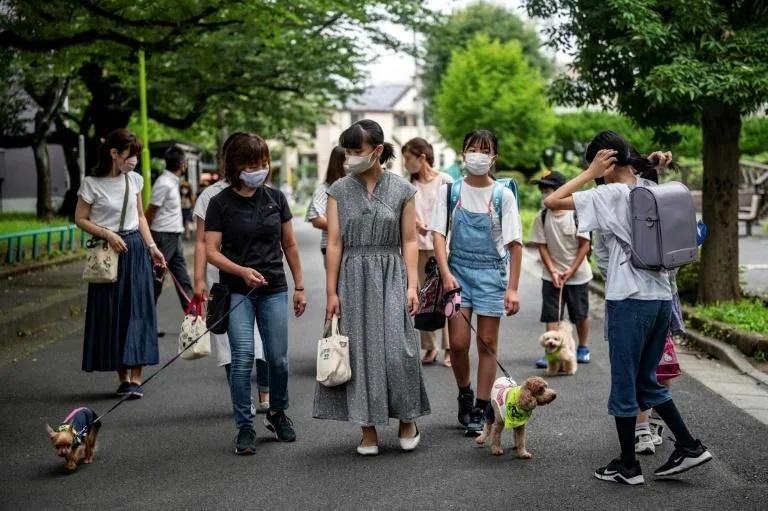 Các thành viên đội tuần tra Wan-wan đi bộ dọc con phố tới một 7. trường tiểu học ở Tokyo hôm 14/7. Ảnh: AFP.