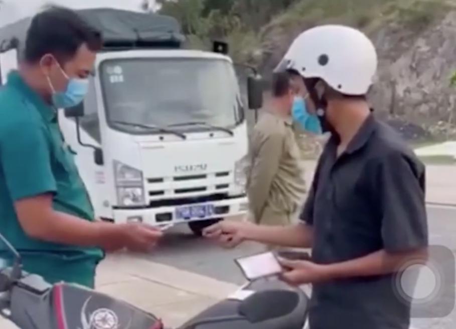 Anh Em (đội mũ bảo hiểm) bị tổ kiểm soát Covid-19 phường Vĩnh Hòa giữ giấy tờ và xe máy, chiều 18/7. Ảnh: Cắt từ video