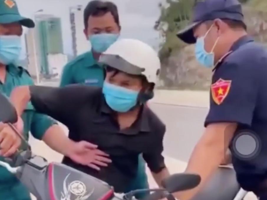 Anh Em (giữa) bị tổ kiểm soát Covid-19 phường Vĩnh Hòa giữ xe máy, chiều 18/7. Ảnh: Cắt từ video.