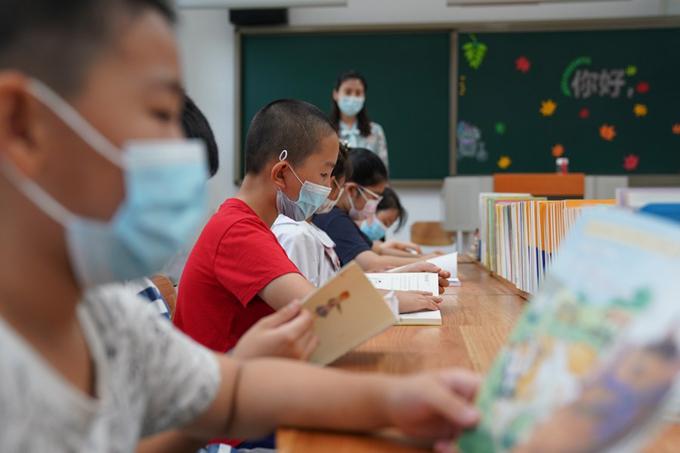 Các em nhỏ đọc sách trong phòng đọc của trường Tiểu học Bắc Kinh, thành phố Bắc Kinh, hôm 19/7. Ảnh: Xinhua.