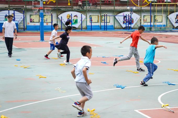 Các em nhỏ tham gia hoạt động ngoài trời, dưới sự hướng dẫn của thầy giáo tại trường Tiểu học Bắc Kinh, thành phố Bắc Kinh, hôm 19/7. Ảnh: Xinhua.