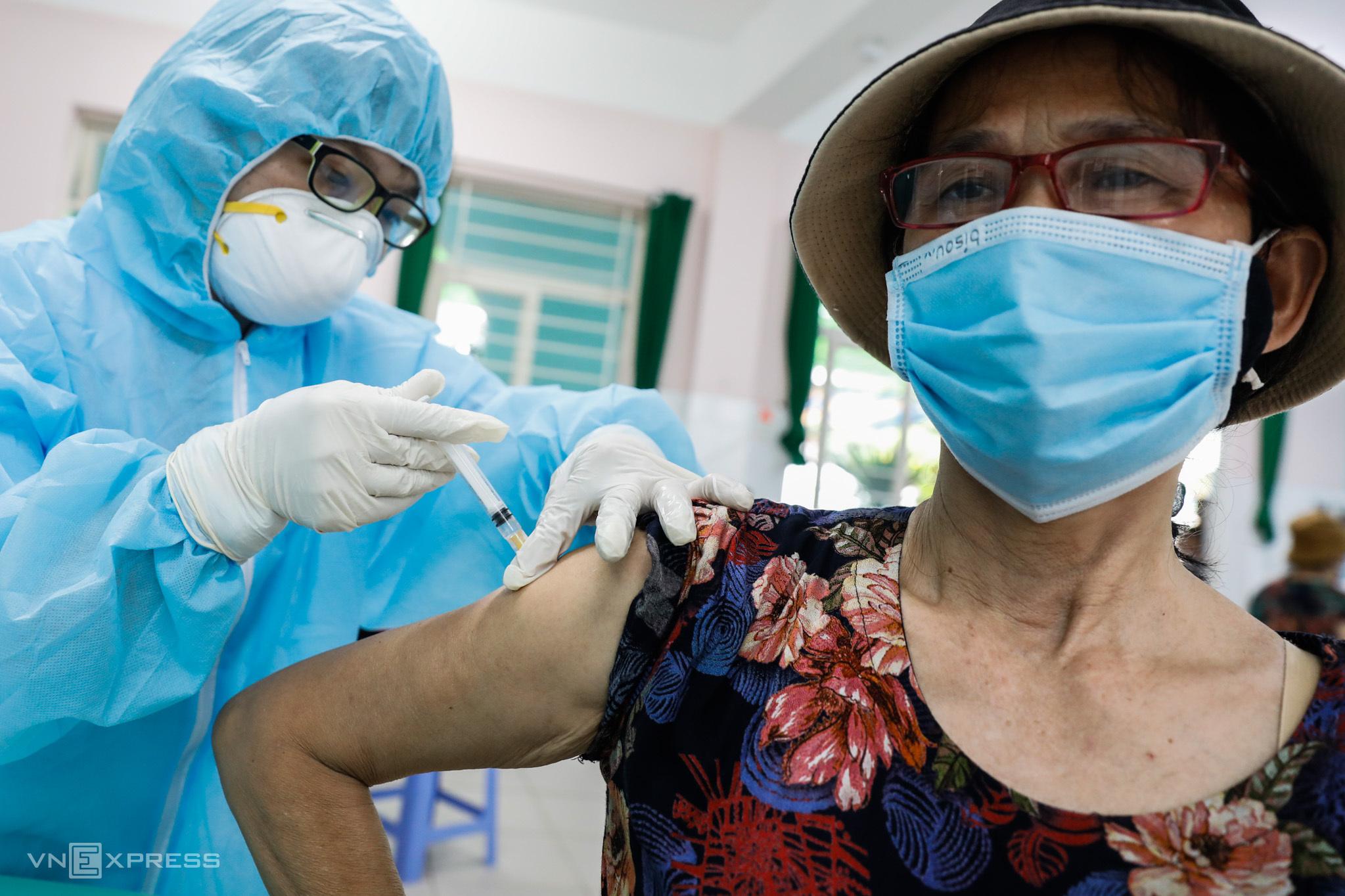 Một người phụ nữ ngoài 60 tuổi tiêm vaccine Covid-19 ở TP HCM hồi tháng 6. Ảnh: Hữu Khoa.