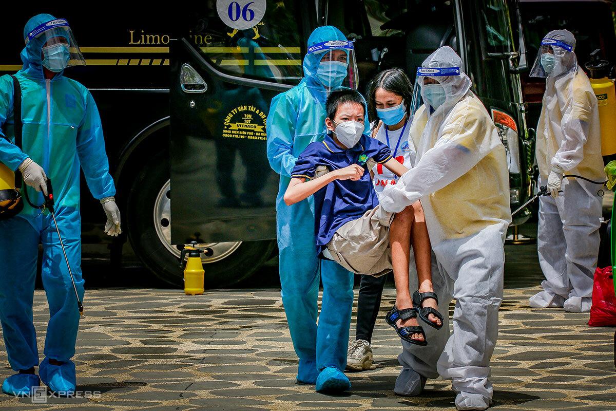 Lực lượng vận chuyển hỗ trợ một người tàn tật về khách sạn cách ly. Ảnh: Quang Nguyễn.
