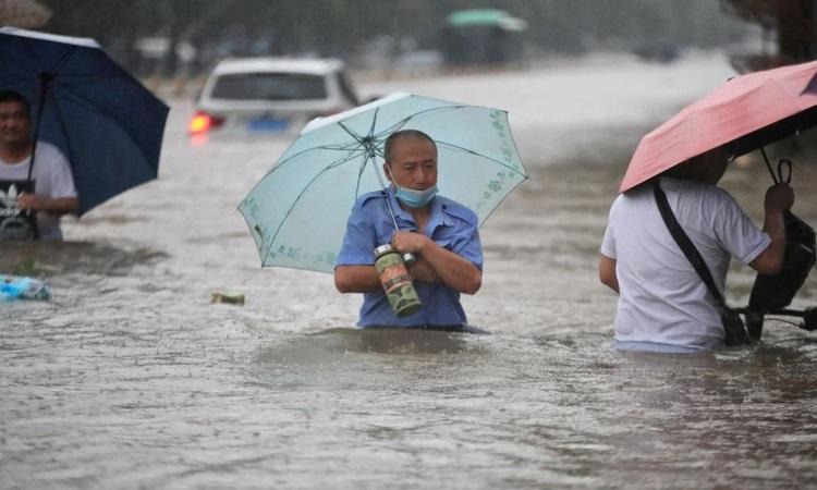 Người dân lội trong nước lũ ở Trịnh Châu. Ảnh: Reuters.