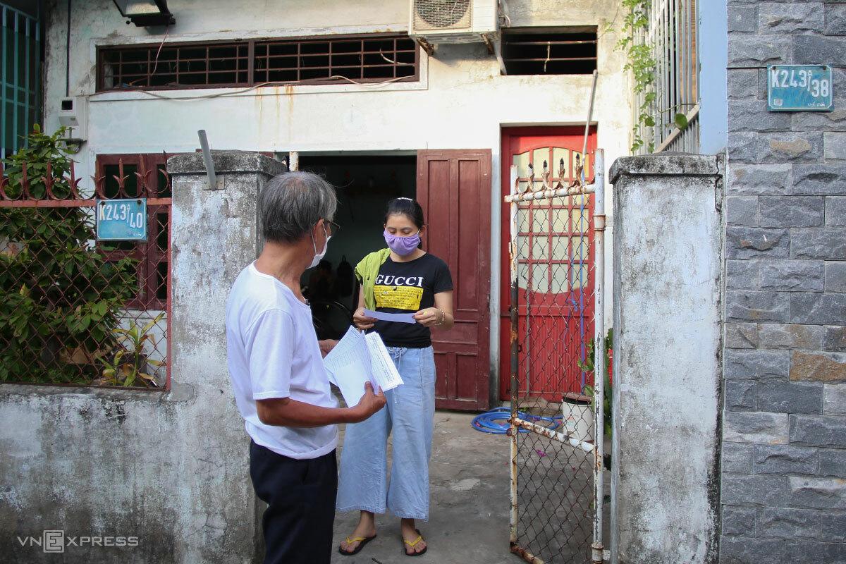 Thành viên tổ Covid cộng đồng ở Đà Nẵng phát phiếu xét nghiệm diện rộng cho người dân. Ảnh: Nguyễn Đông.