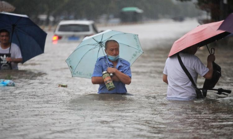 Người dân lội qua dòng nước lũ trên đường phố Trịnh Châu, tỉnh Hà Nam, Trung Quốc, hôm 20/7. Ảnh: China Daily.
