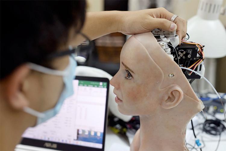 Kỹ sư điều chỉnh phần đầu của robot hình người Grace. Ảnh: Reuters.