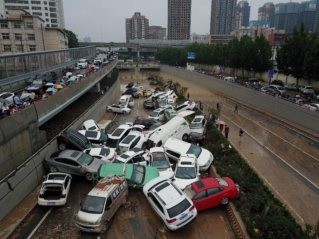 Người dân đứng từ trên cao nhìn xuống ô tô hư hỏng sau trận lũ ở Trịnh Châu ngày 22/7. Ảnh: AFP.