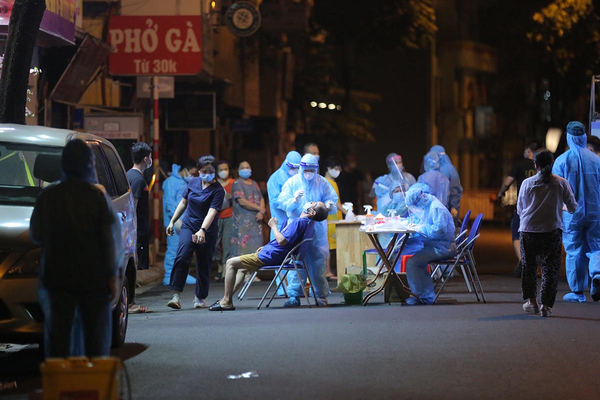 Hơn 100 người ở phố Thụy Khuê được lấy mẫu xét nghiệm nhanh rạng sáng 22/7. Ảnh: Ngô Trần.