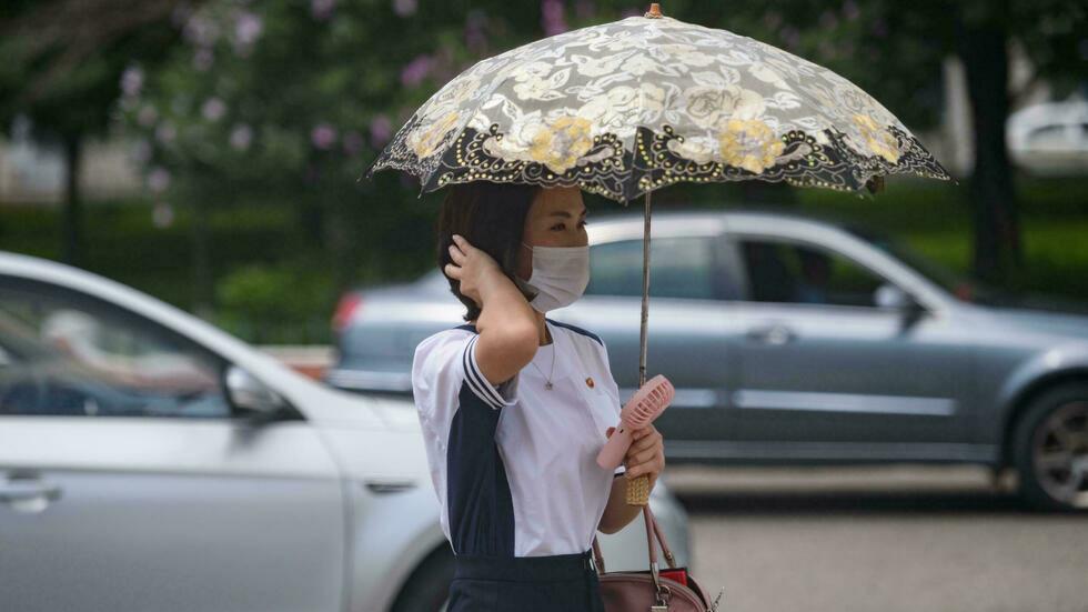 Một phụ nữ che ô, tay cầm quạt làm mát trên đường phố Bình Nhưỡng hôm 21/7. Ảnh: AFP.