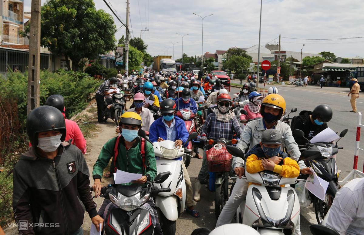 Người dân đứng hàng dài để quá chốt kiểm dịch ở xã Điện Thắng Bắc, thị xã Điện Bàn trước khi vào Quảng Nam, trưa 22/7. Ảnh: Đắc Thành.