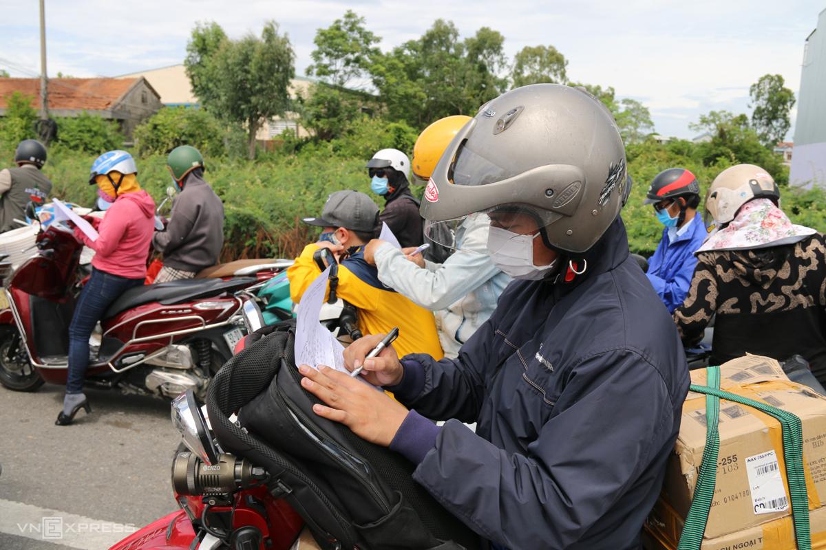 Một người dân ngồi trên xe máy khai báo y tế để  qua chốt vào Quảng Nam, trưa 22/7. Ảnh: Đắc Thành.
