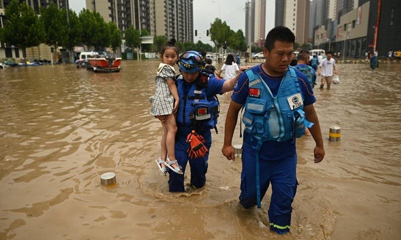Các thành viên đội cứu hộ bế một bé gái băng qua đường phố ngập lụt sau mưa lớn ở Trịnh Châu, tỉnh Hà Nam, Trung Quốc hôm nay. Ảnh: AFP.