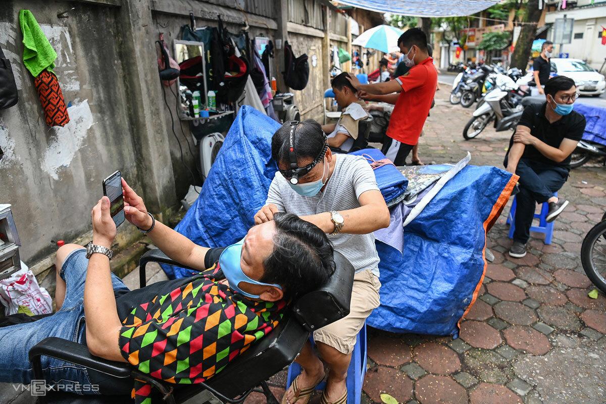Tiệm cắt tóc vỉa hè nhộn nhịp hồi cuối tháng 6 khi Hà Nội cho mở lại một số dịch vụ. Ảnh: Giang Huy