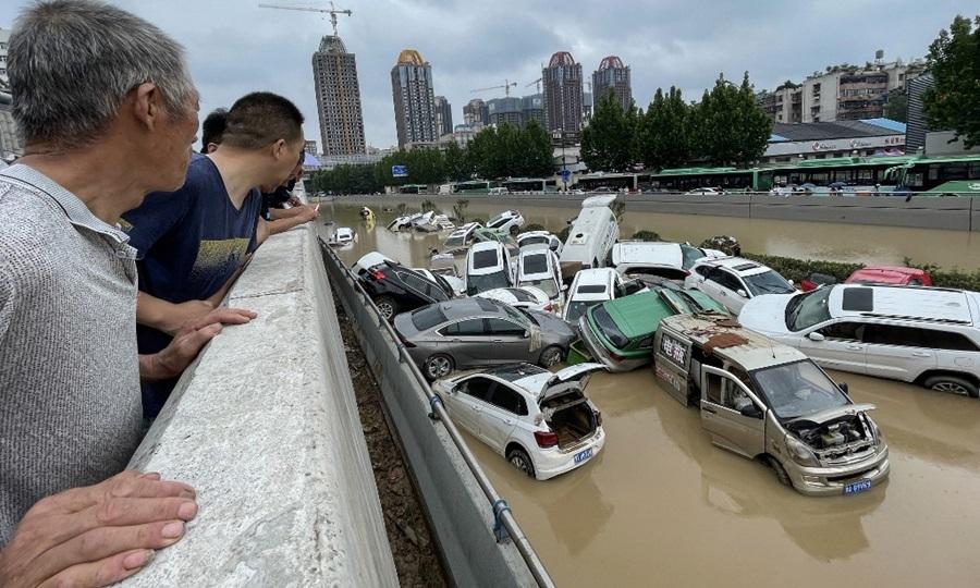 Người dân quan sát những chiếc ngập trong nước lũ ở thành phố Trịnh Châu, tỉnh Hà Nam, Trung Quốc hôm 21/7. Ảnh: AFP.