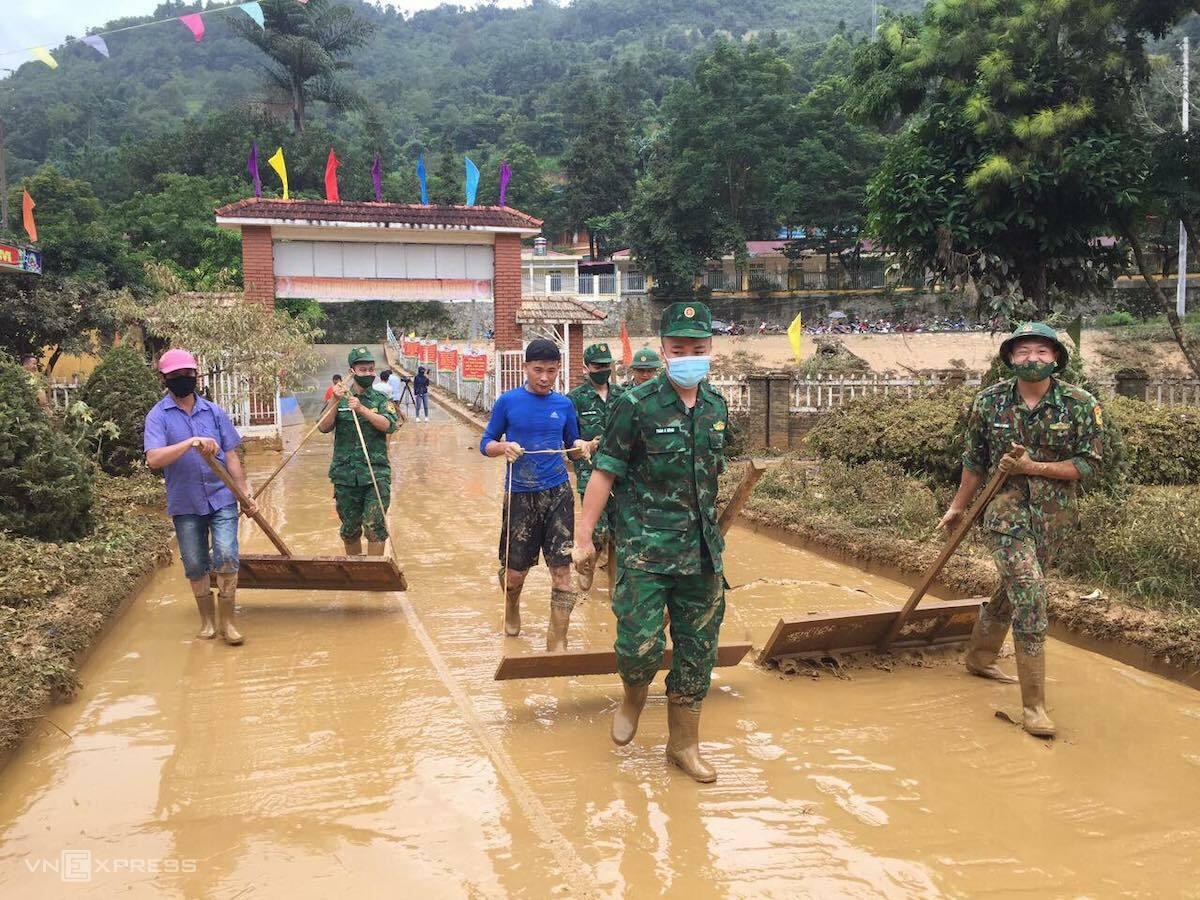 Bộ đội, công an, người dân và giáo viên khắc phục hậu quả sau lũ. Ảnh: Nguyễn Chỉnh