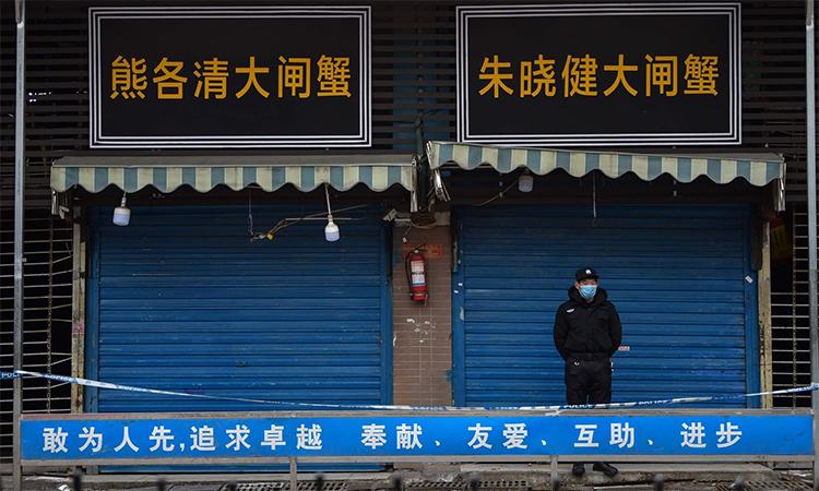 Cảnh sát đứng gác trước chợ hải sản Hoa Nam tại thành phố Vũ Hán, Trung Quốc, hồi tháng 1/2020. Ảnh: AFP.