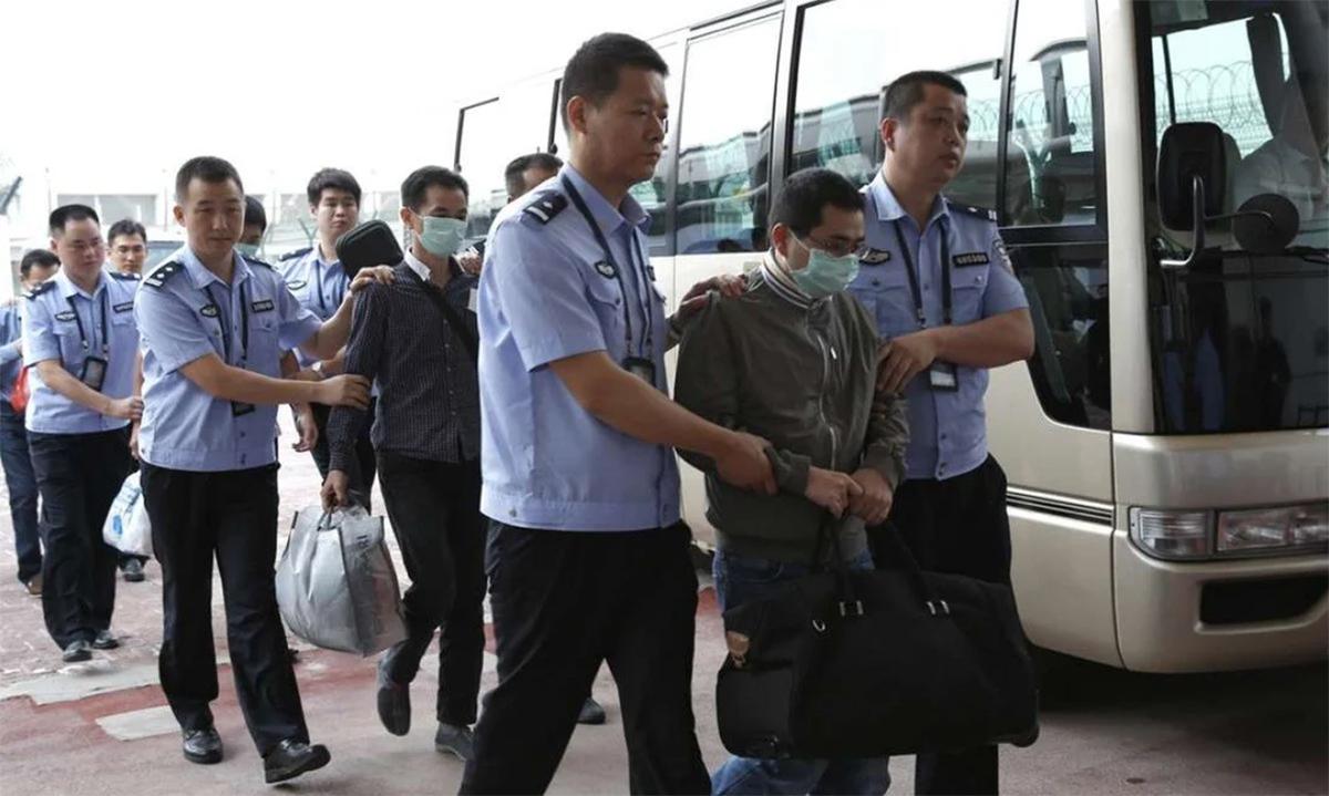 Các nghi phạm Trung Quốc bị áp giải ra xe sau khi bị dẫn độ từ Indonesia về nước tháng 6/2015. Ảnh: Xinhua.