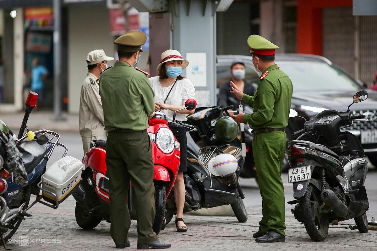 Lực lượng công an nhắc nhở người dân ra đường không có lý do chính đáng. Ảnh: Nguyễn Đông.
