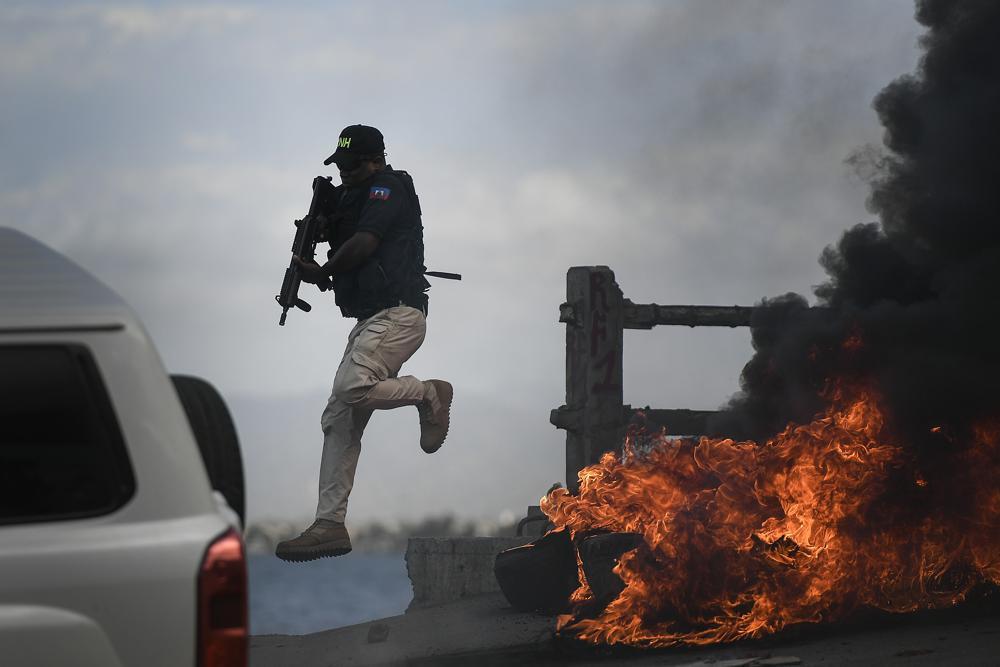 Cảnh sát vũ trang Haiti bỏ xe tháo chạy ở Cap-Haiten khi biểu tình leo thang bạo lực ngày 22/7. Ảnh: AP