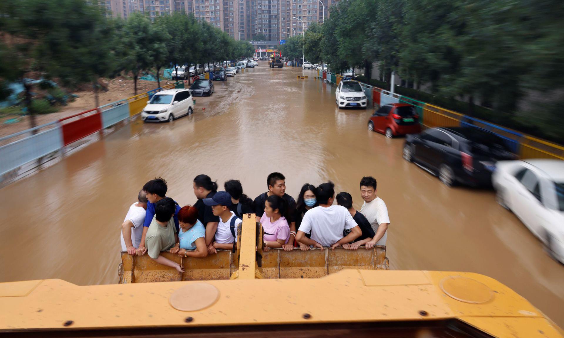 Người dân được đưa khỏi vùng ngập lụt bằng máy xúc tại thành phố Trịnh Châu, tỉnh Hà Nam, Trung Quốc, hôm nay. Ảnh: Reuters.