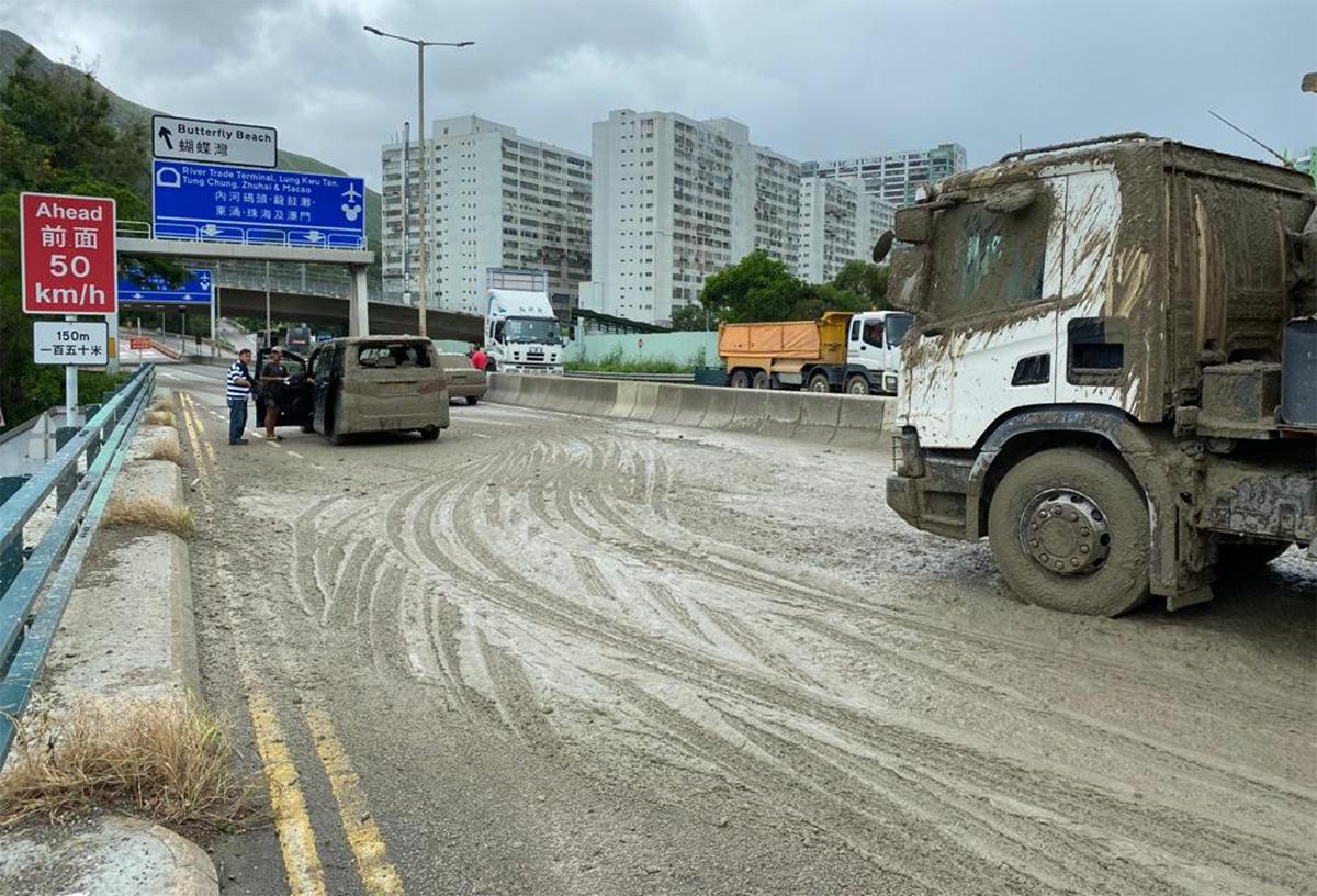 Hai ôtô con tắm bùn, mặt đường cũng phủ đầy bùn đất trong khi đầu xe ben cũng bị bẩn. Ảnh: HK01