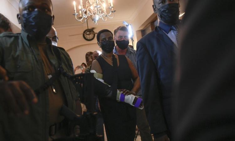 Đệ nhất phu nhân Haiti Martine Moise được hộ tống tại lễ tưởng niệm chồng ở khách sạn Roi Christophe, Cap-Haitien, hôm 22/7. Ảnh: AP.