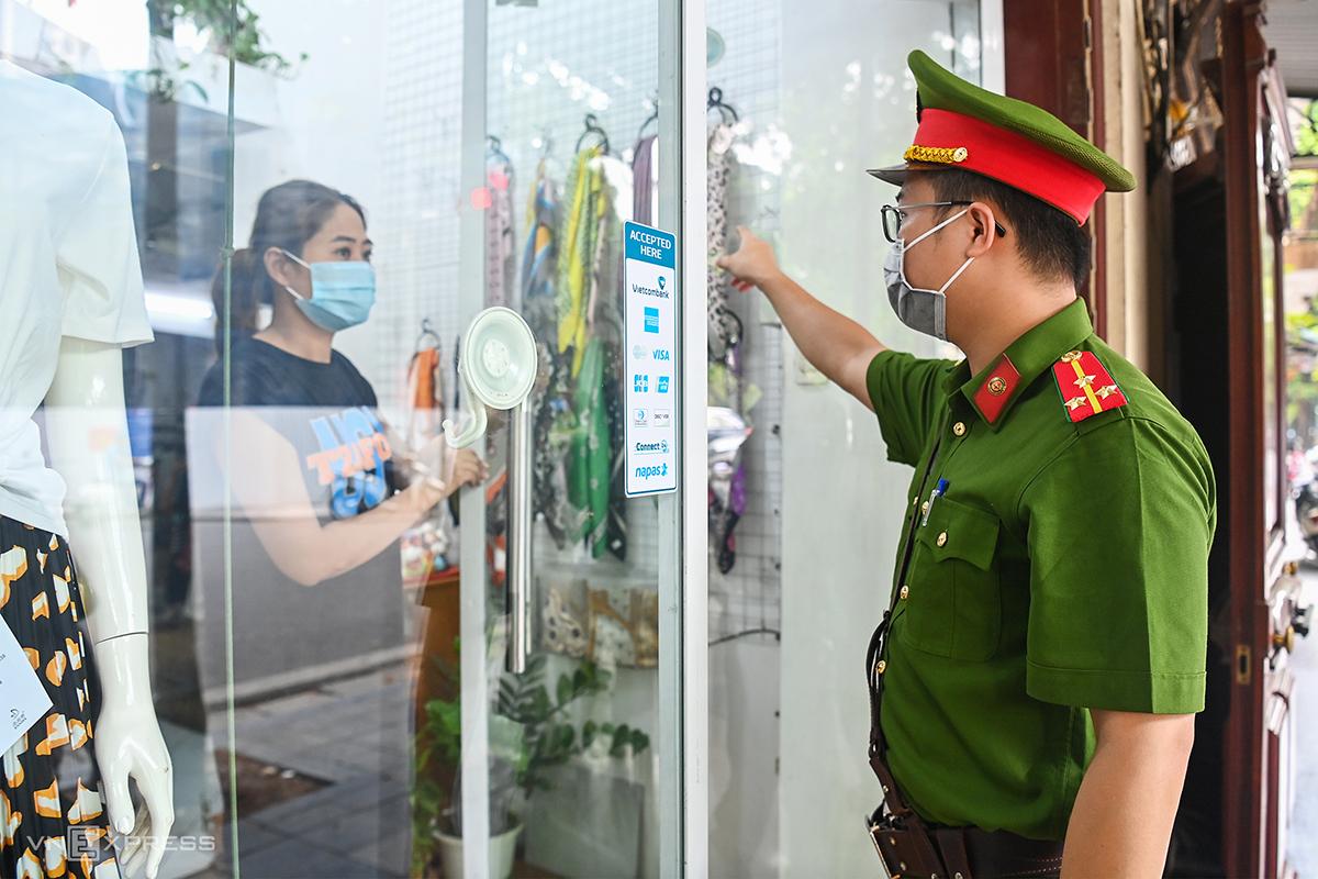 Công an nhắc nhở các hộ dân ở Hà Nội. Ảnh: Giang Huy.
