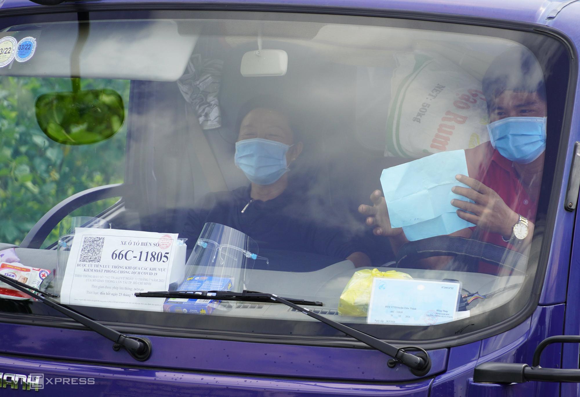 Một xe tải chở hàng có giấy ưu tiên được dán ở kính lái tại chốt quốc lộ 1, xã Tân Hương, huyện Châu Thành, tỉnh Tiền Giang. Ảnh: Hoàng Nam
