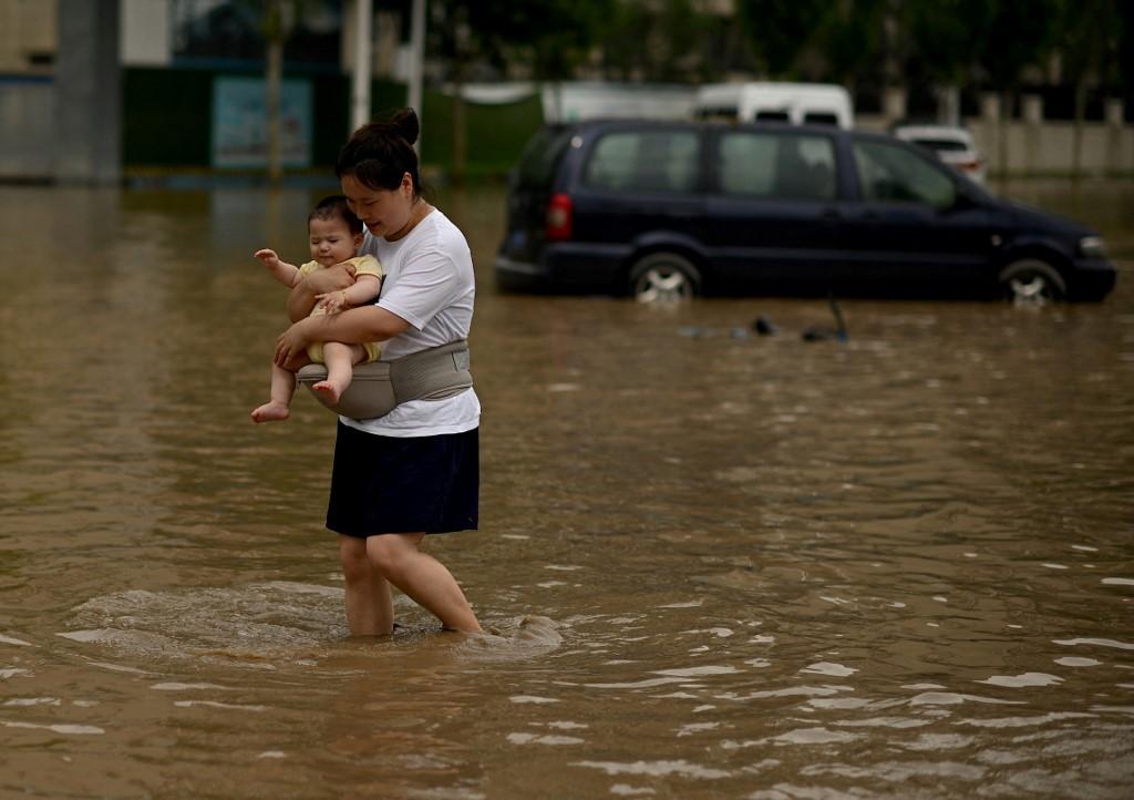 Một bà mẹ ôm con đi trong nước lũ ở Trịnh Châu ngày 22/7. Ảnh: AFP.