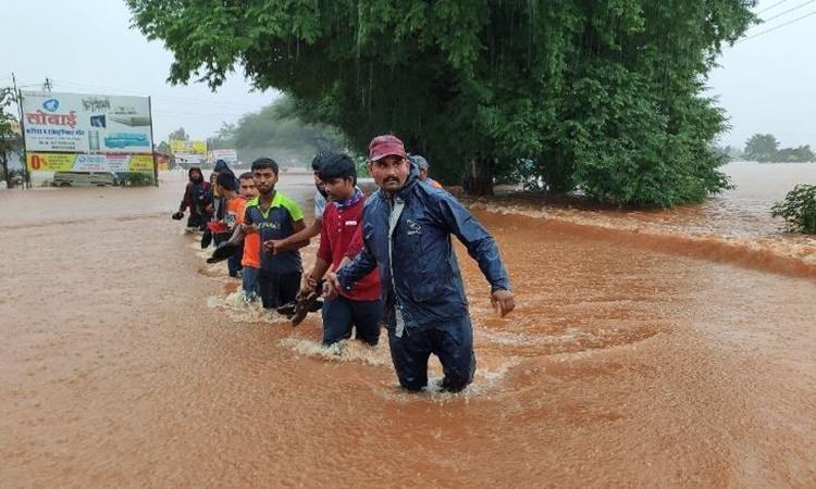 Nhân viên cứu hộ giải cứu những người dân mắc kẹt do mưa lũ ở thành phố Kolhapur, bang Maharashtra, phía tây Ấn Độ, ngày 23/7. Ảnh: AP.