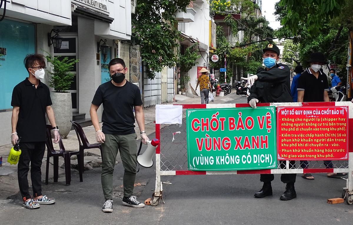 Lực lượng tình nguyện viên và công an chốt bảo vệ vùng xanh hướng dẫn người dân nhận hàng hóa tại cổng chính cư xá Đô Thành. Ảnh: Hà An.
