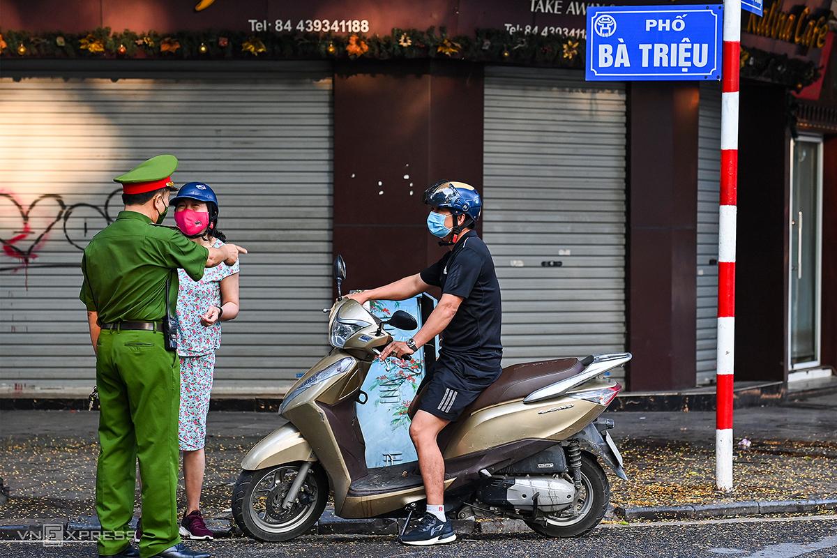Công an phường ở Hà Nội nhắc nhở người dân về nhà nếu không có nhu cầu cần thiết. Ảnh: Giang Huy.